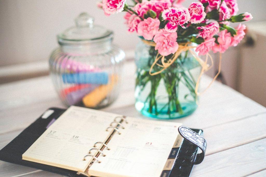 kalender på bord med blommor och godis i en burk