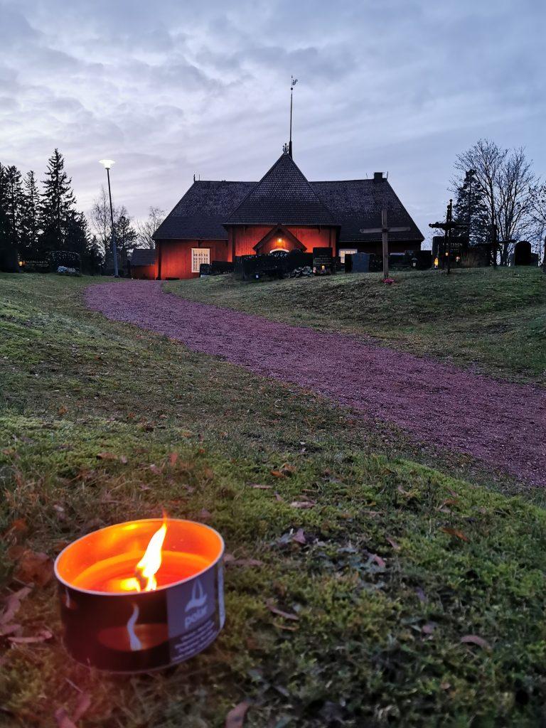Bild av Houtskärs kyrka med en fackla i förgrunden