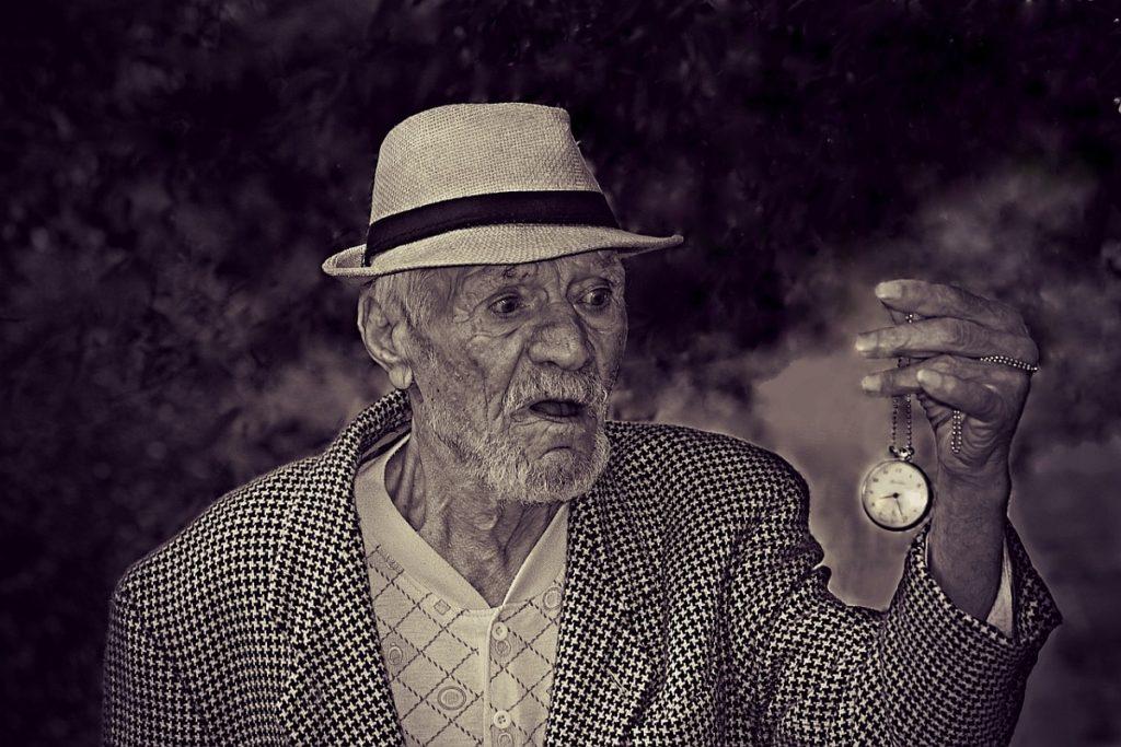 gammal man som häpet ser på en klocka