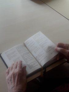 Uppslagen psalmbok och två händer.