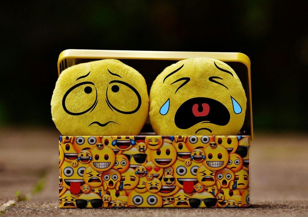 En låda täckt av emoijs och i den två mjukisemojin som ser ledsna ut.